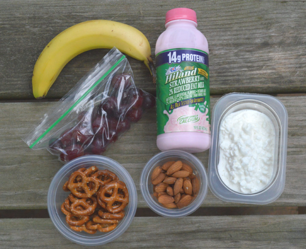 bananas, grapes in bag, Hiland dairy strawberry milk, pretzels, almonds and cottage cheese on a picnic table