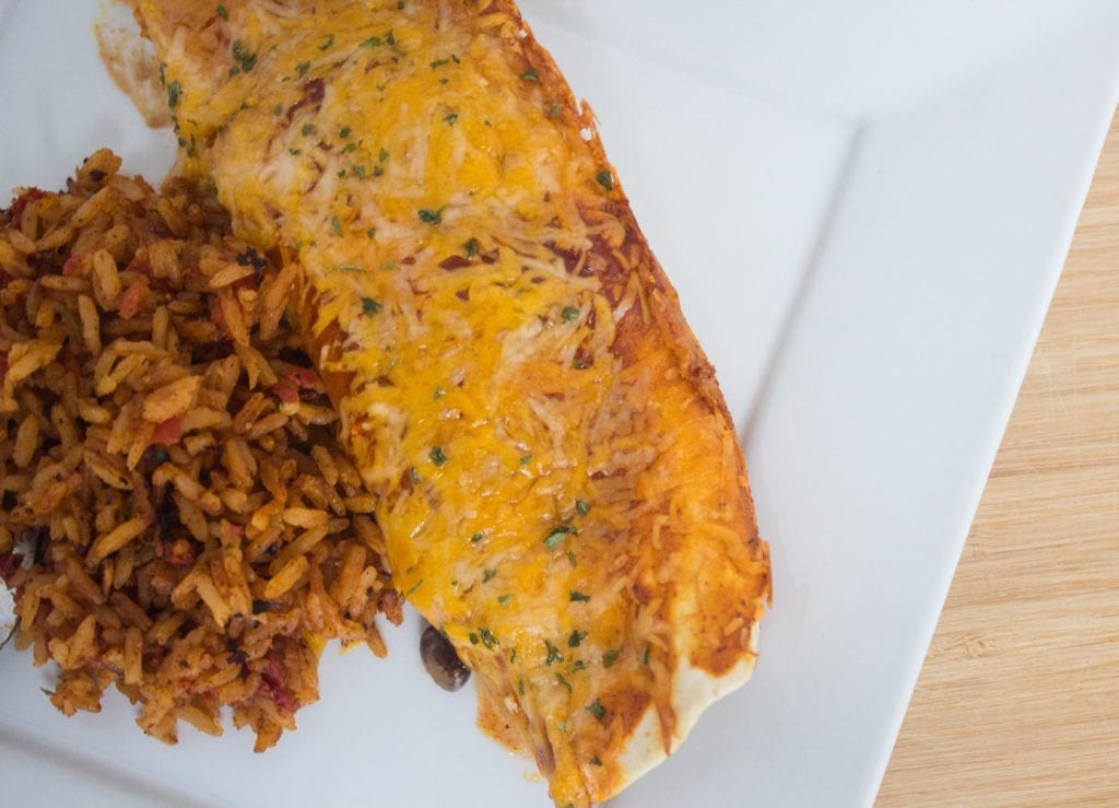 Chicken enchiladas and mexican rice plated