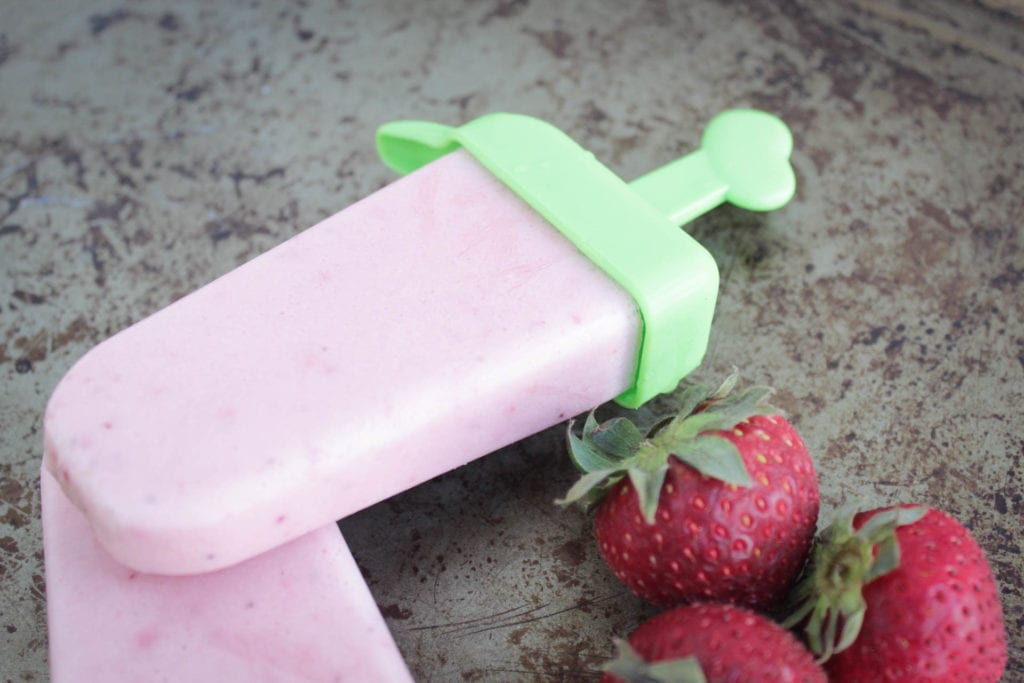 strawberry cheesecake popsicle in a popsicle mold with fresh strawberries