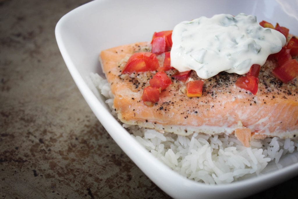 Baked salmon with tomatoes and basil mayo sauce over rice in a white bowl