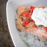 baked salmon with tomatoes and basil mayo over rice in a white bowl