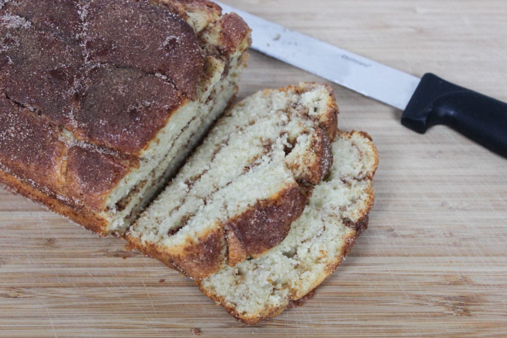 Sliced cinnamon loaf bread on cutting board with knife in background