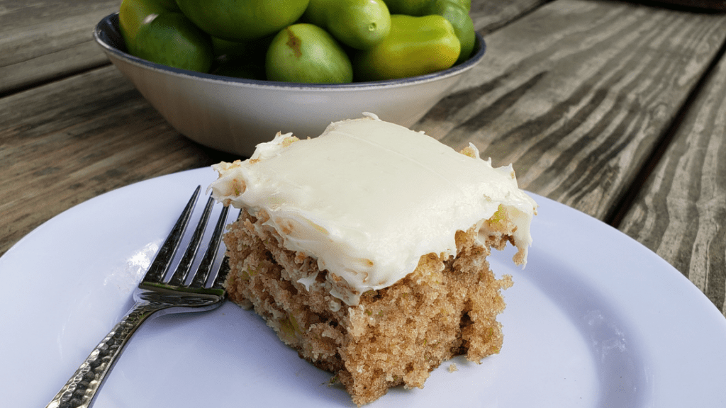 green tomato cake with cream cheese frosting on a white plate
