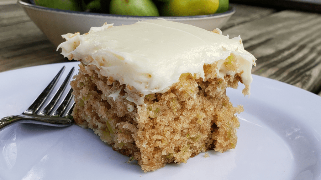 Slice of green tomato cake with cream cheese frosting on white plate