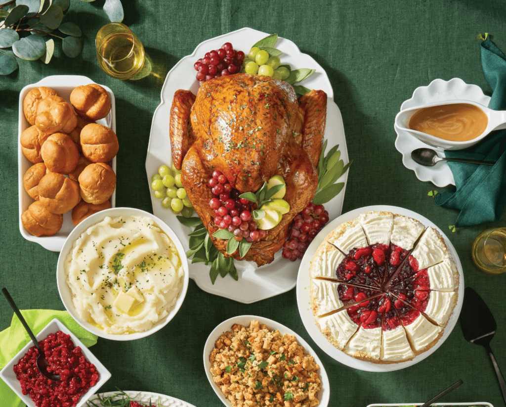 Turkey, mashed potatoes, rolls, cherry pie, cranberry sauce, stuffing and gravy on green tablecloth