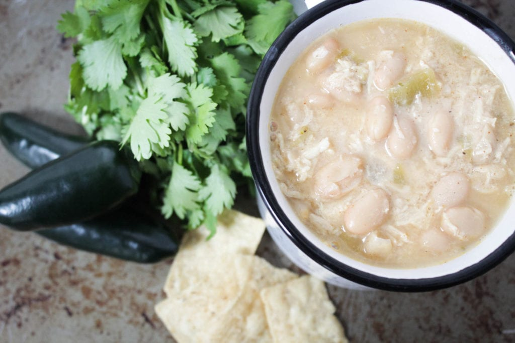 White chicken chili in bowl with tortilla chips