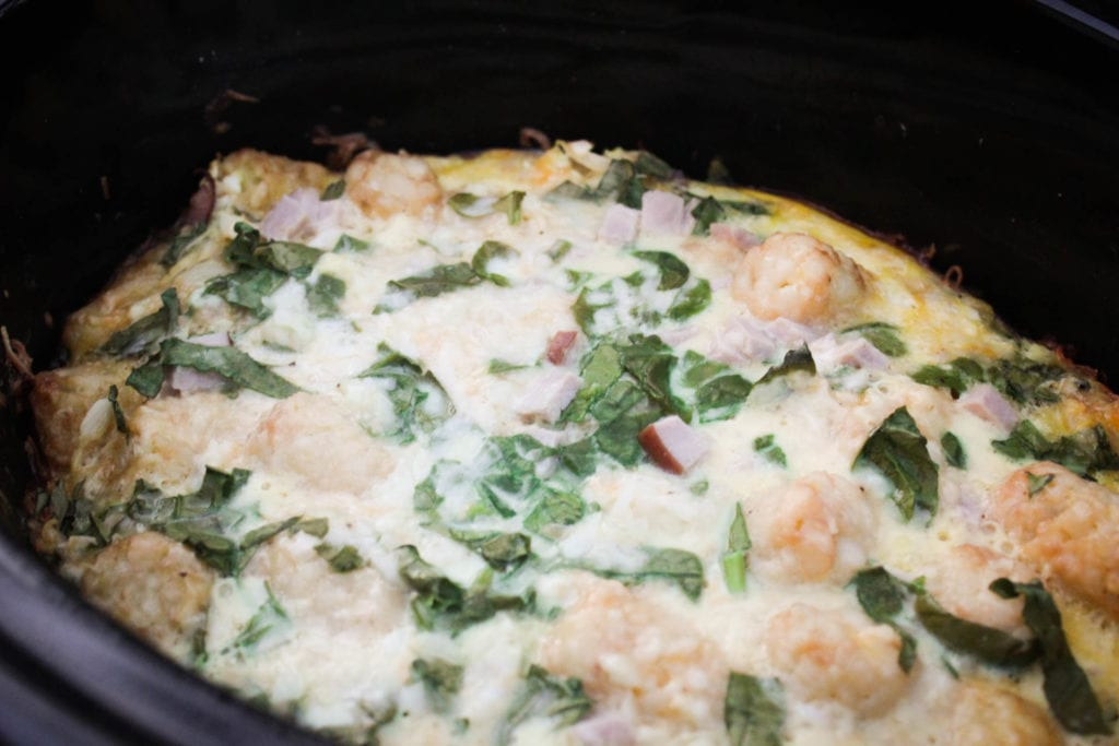 Egg casserole with ham, cheese, tater tots, spinach and onion made in the slow cooker