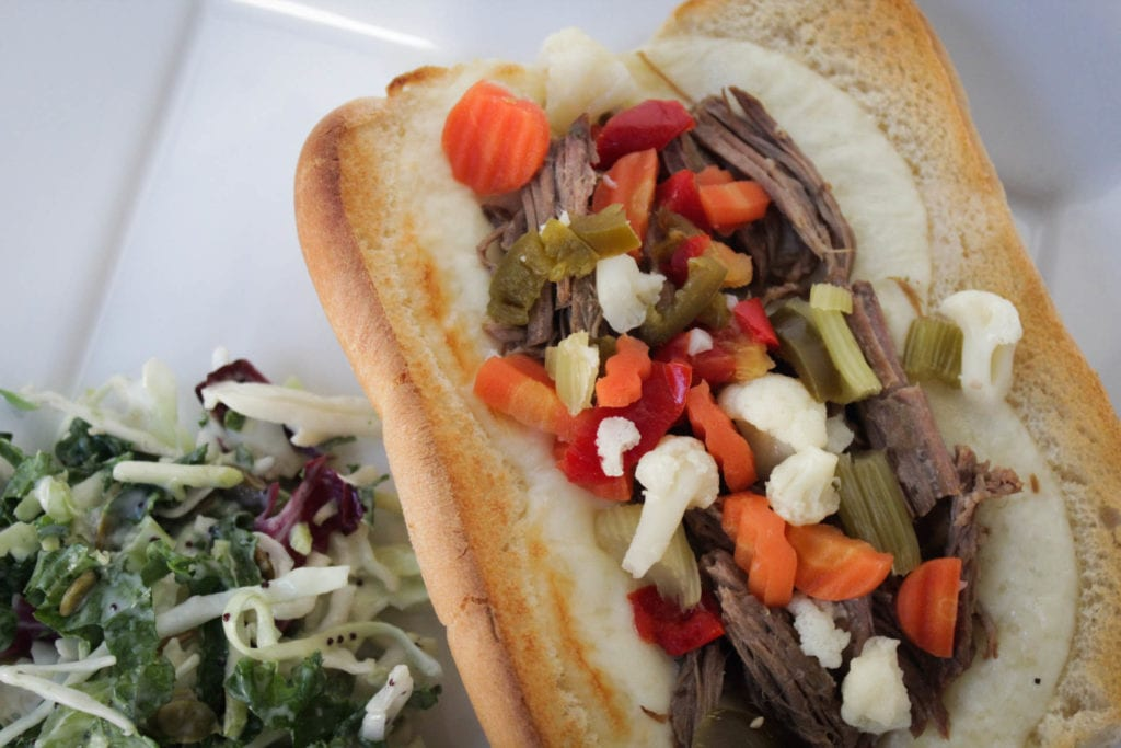 Hot Italian beef sandwiches with provolone cheese and Giardiniera served with a side salad