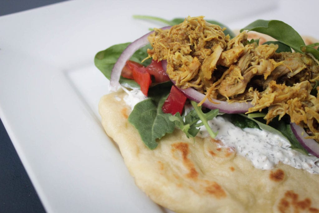 Crock pot chicken shawarma Indian cuisine served on naan or pita bread with greens, diced tomatoes, red onions and dill sauce