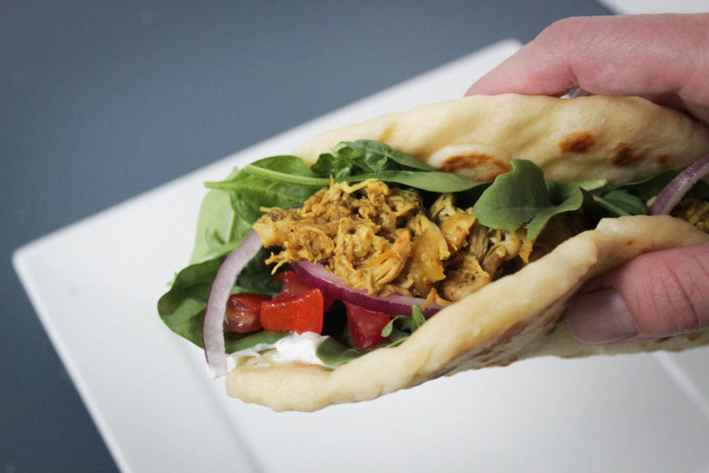 Crock Pot chicken shawarma served in naan bread with mixed greens, diced tomatoes, red onion and tzatziki sauce