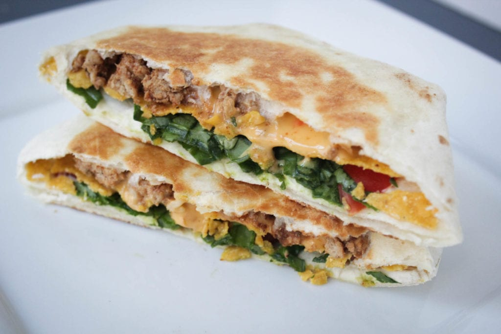 crunchwrap supreme copycat recipe with taco meat, cheese, tomatoes, sour cream, spinach and toasted in a burrito