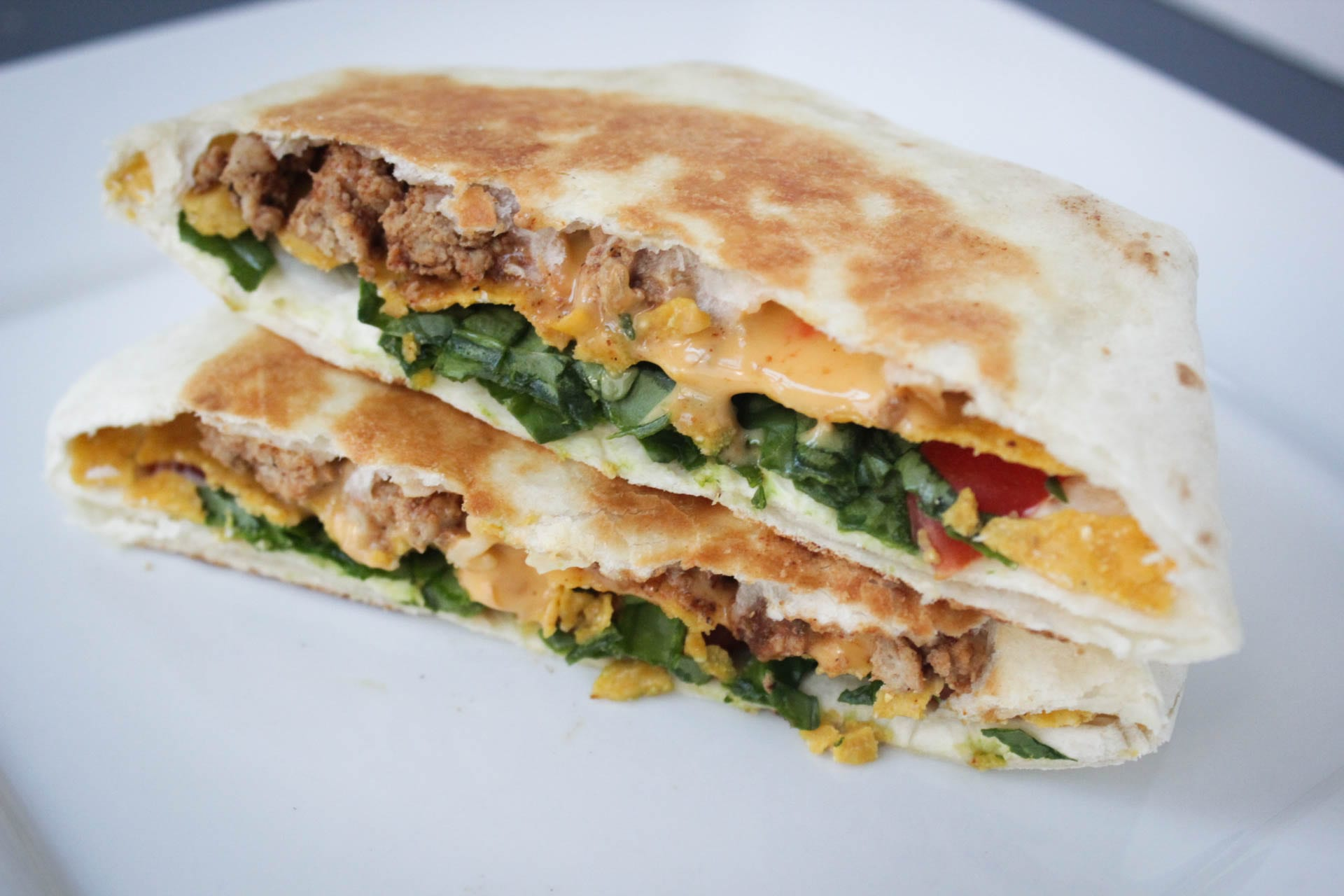 Copycat crunchwrap supreme recipe with 7 ingredients - tortilla shells, taco meat, sour cream, cheese sauce, tostadas, lettuce and tomatoes