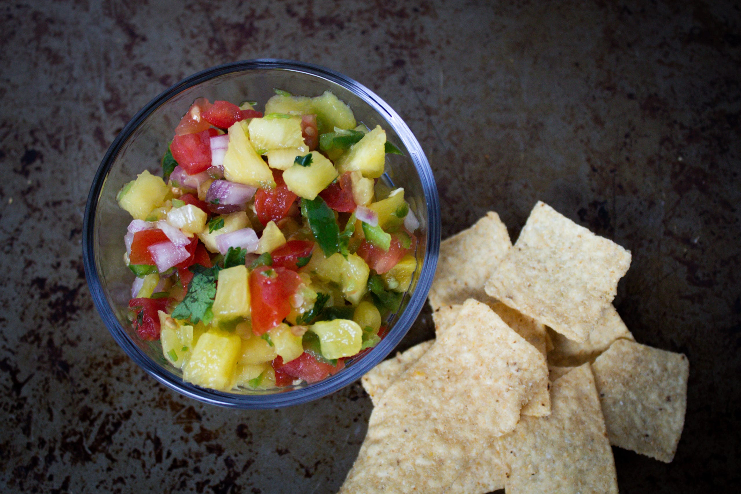 Bowl of pineapple salsa with fresh pineapple, tomatoes, red onion, jalapeno, cilantro and lime served with chips