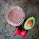 strawberry chocolate smoothie in glass jar with 2 fresh strawberries and 1/2 avocado next to it
