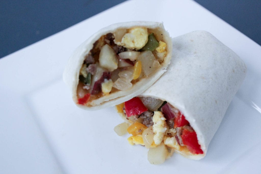 Sausage, eggs, potatoes, onion and red bell pepper in a tortilla on a white plate