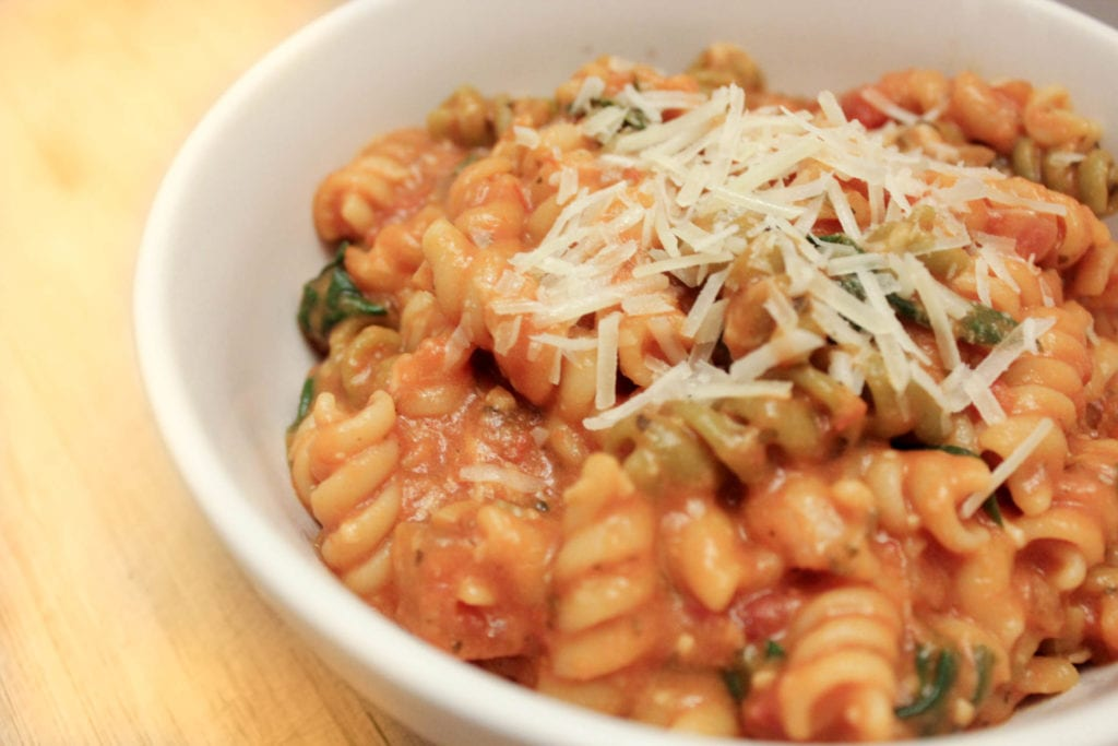 Creamy pasta dish with spinach and tomatoes topped with Parmesan cheese and served in white bowl