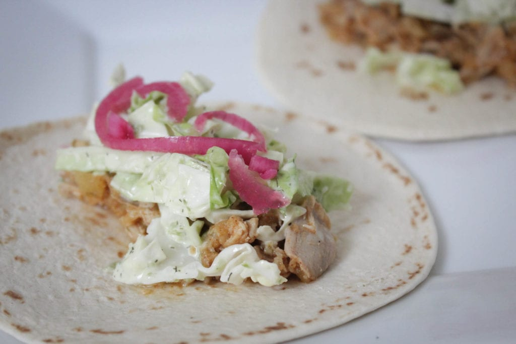 Tortilla shell with slow cooked chicken, spicy slaw, pickled red onion and cabbage