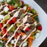 big mac salad with lettuce, tomatoes, ground beef, diced pickles, shredded carrots, white onions and drizzled with thousand island