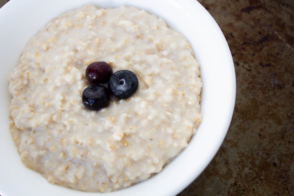 steel cut oats in white bowl with 3 blueberries on top