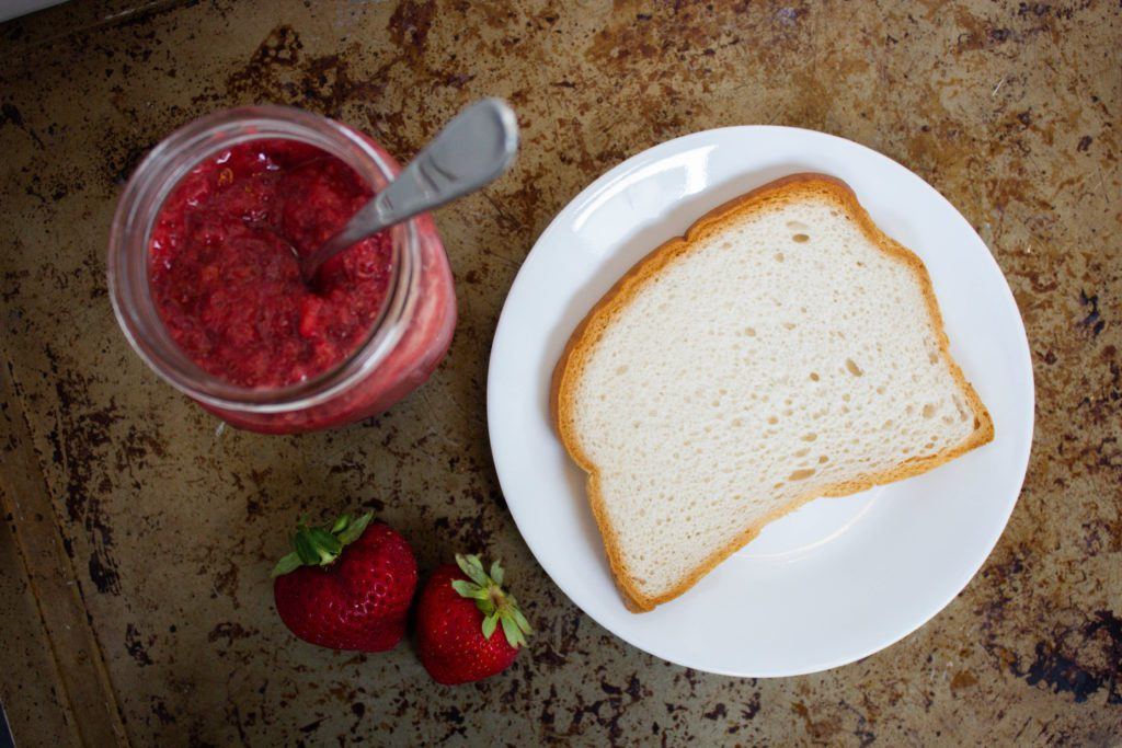 jar of strawberry jam and piece of white bread