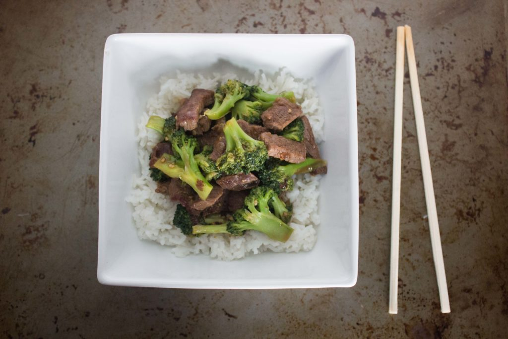 Steak tips and broccoli served over rice in a square bowl with chopsticks placed next to the bowl