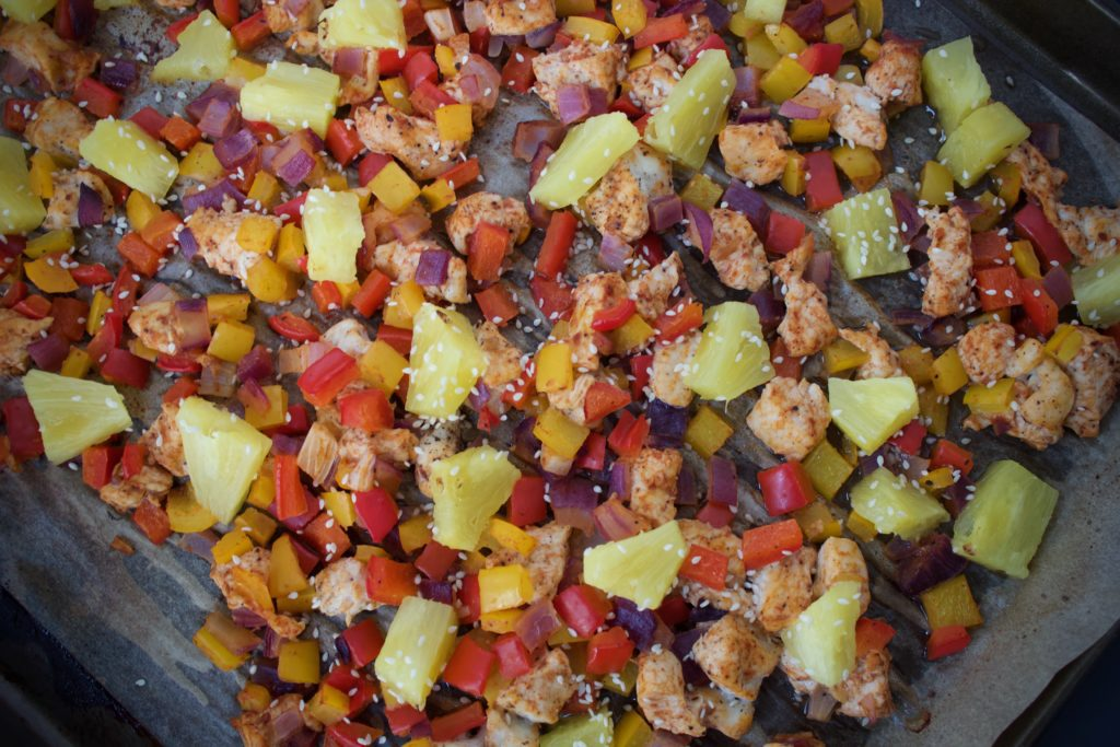 Hawaiian BBQ Chicken with diced bell peppers, onions, and pineapple on a sheet pan