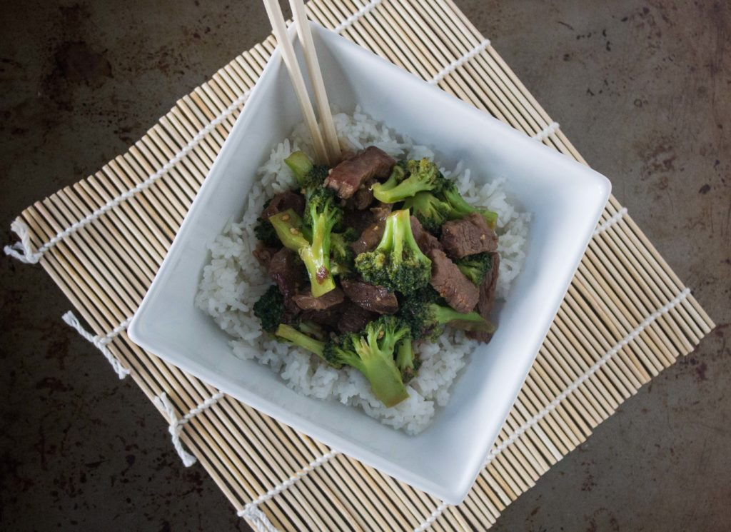 Beef and broccoli over white rice in square bowl with chopsticks
